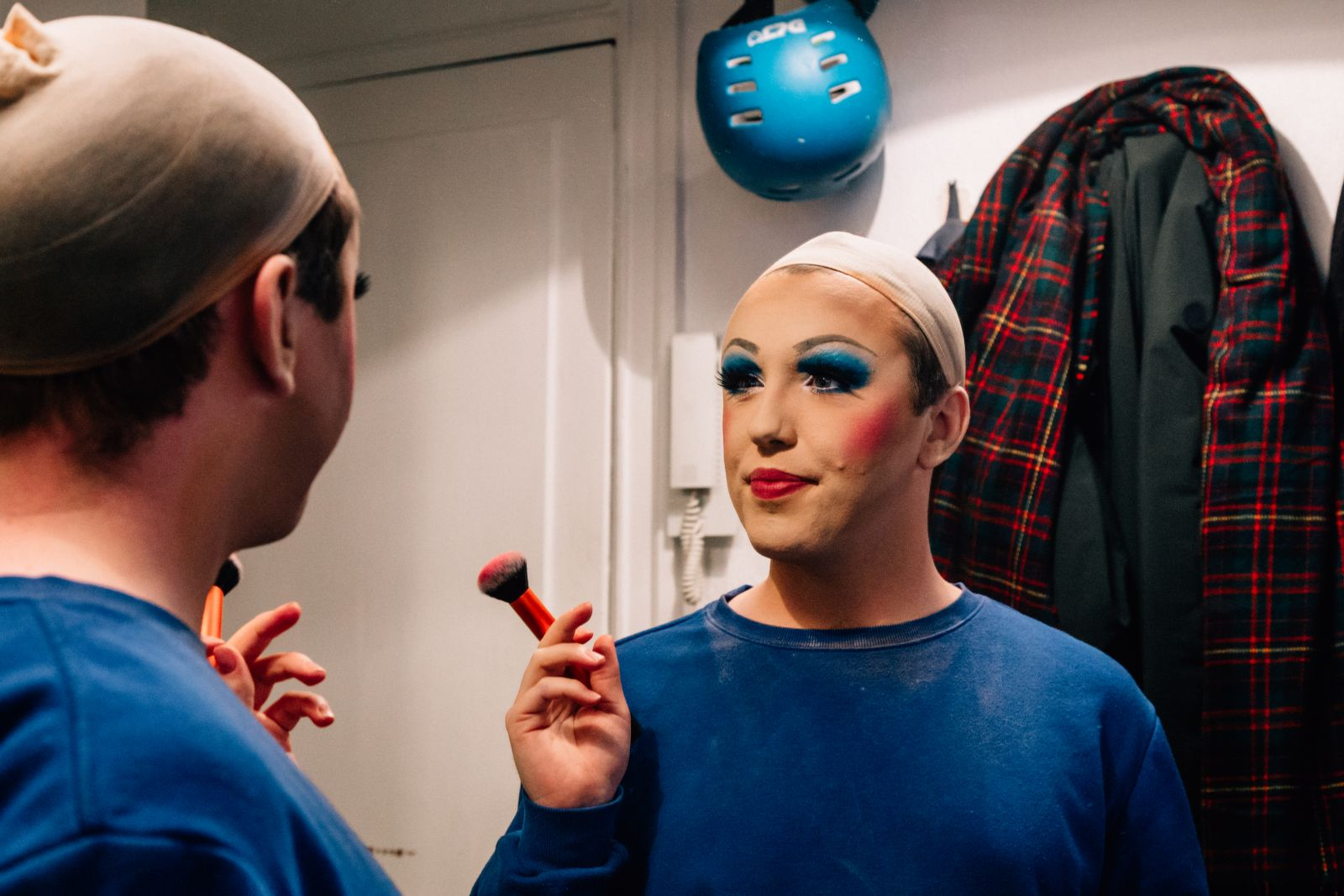 Man with makeup looks into the mirror