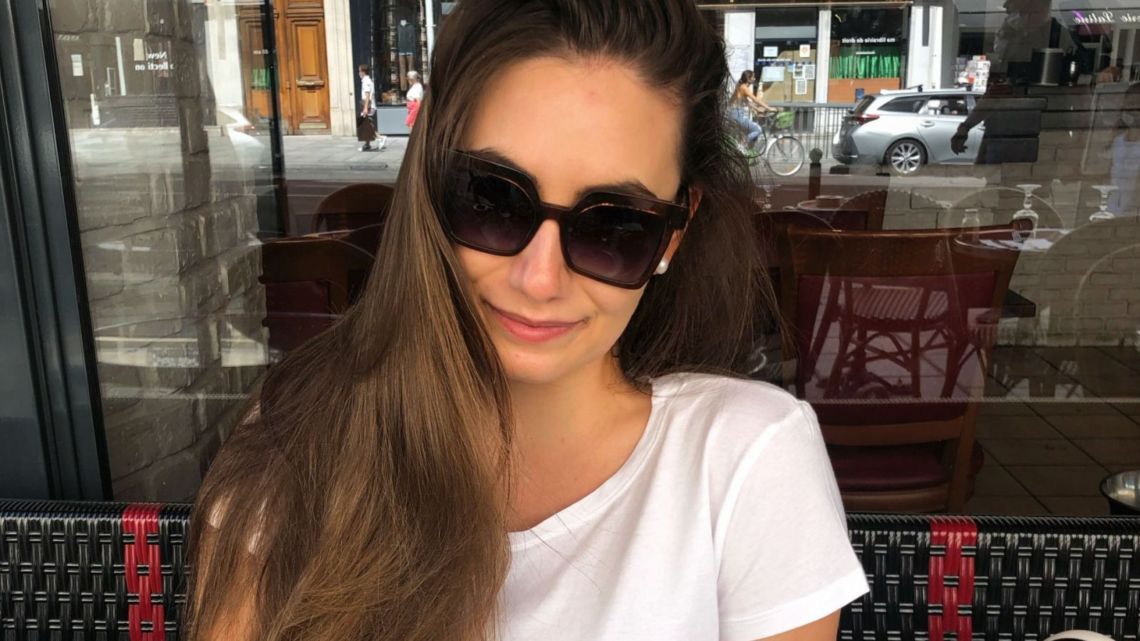 young woman sitting in a restaurant - outside