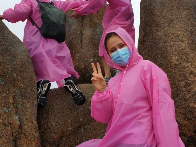 Student with a mask wearing a pink rain coat and
