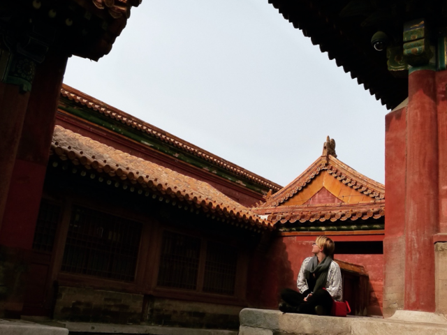 young woman sitting by old house in China