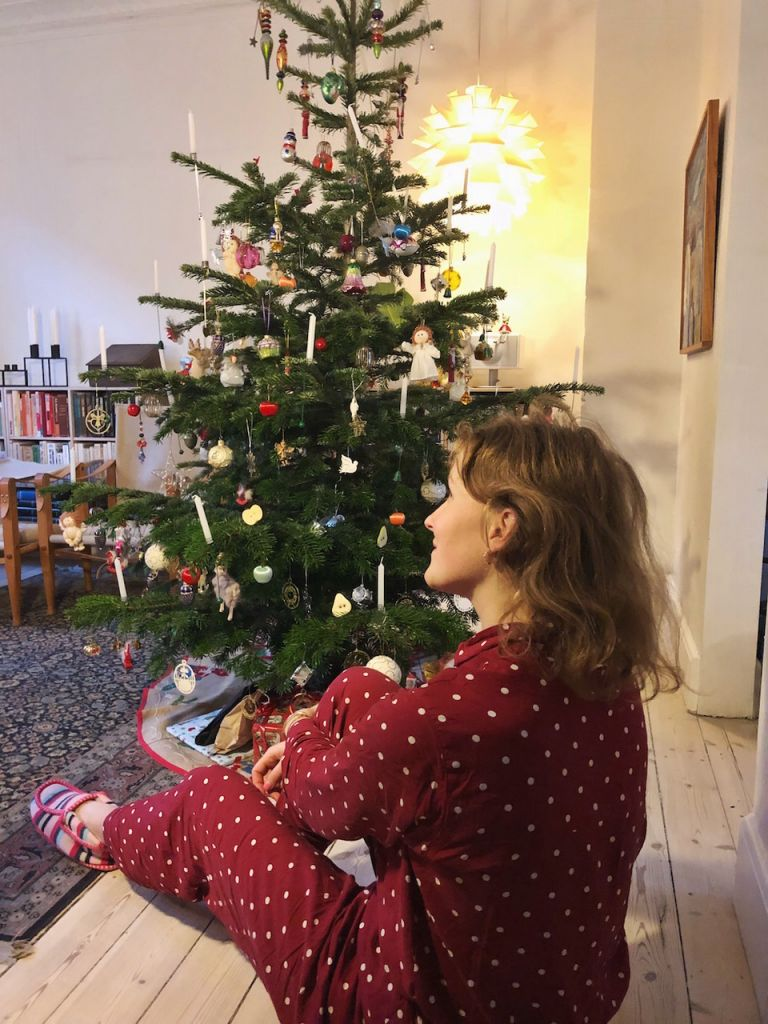 young woman sitting by christmas tree
