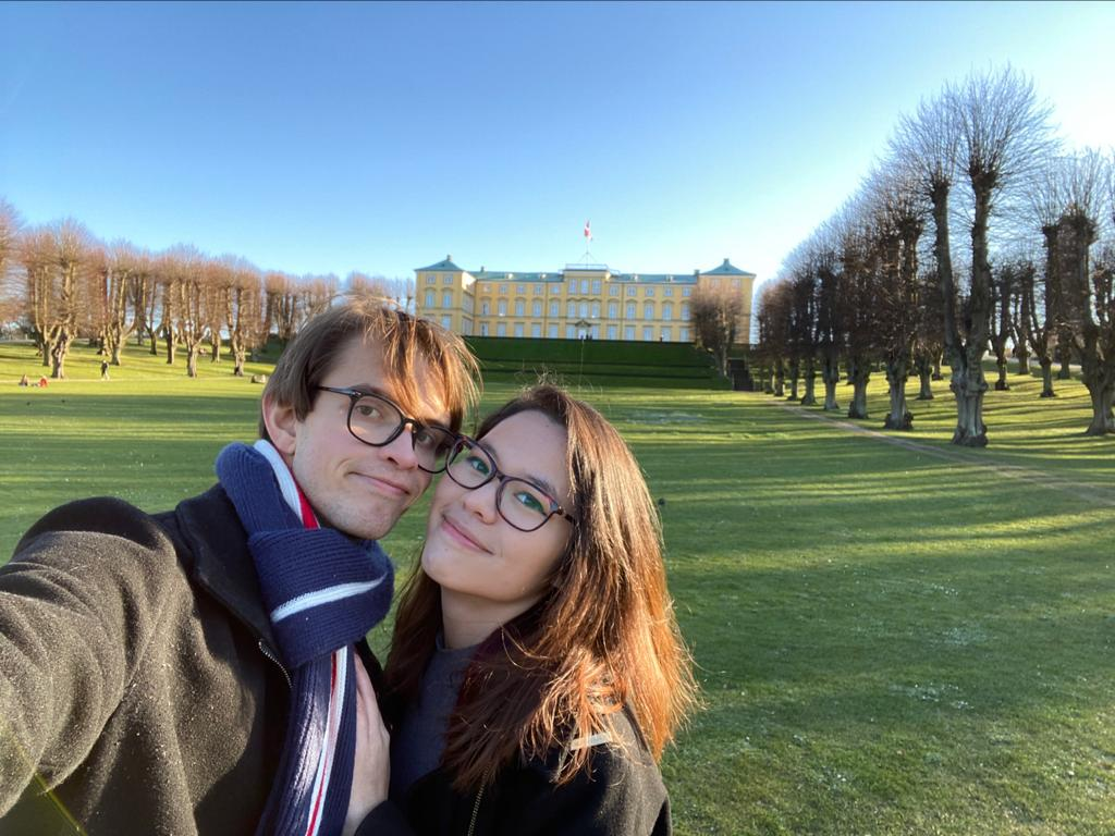 A couple smiling in front of Frederiksberg Castle