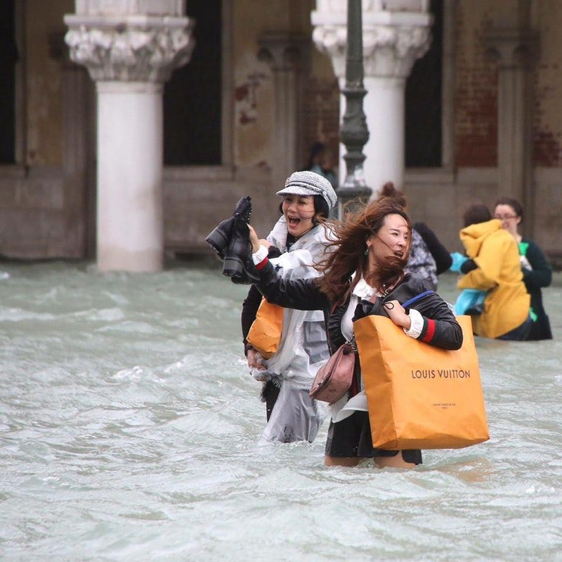 Tourists walking through flood in Venice