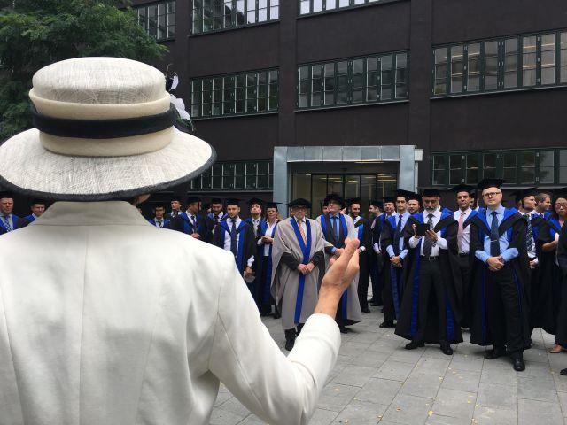 Woman in white speaking to graduates