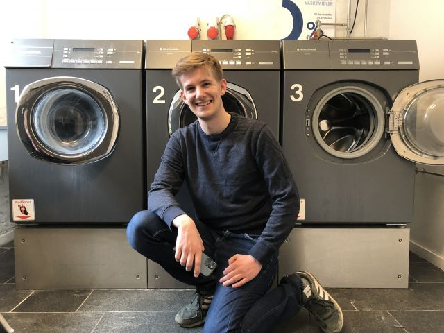 Man sitting in front of washing machines