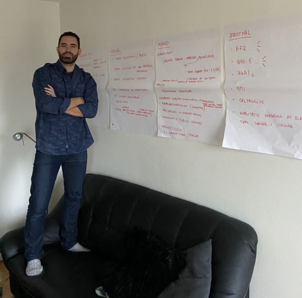 man stands in his sofa with some posters