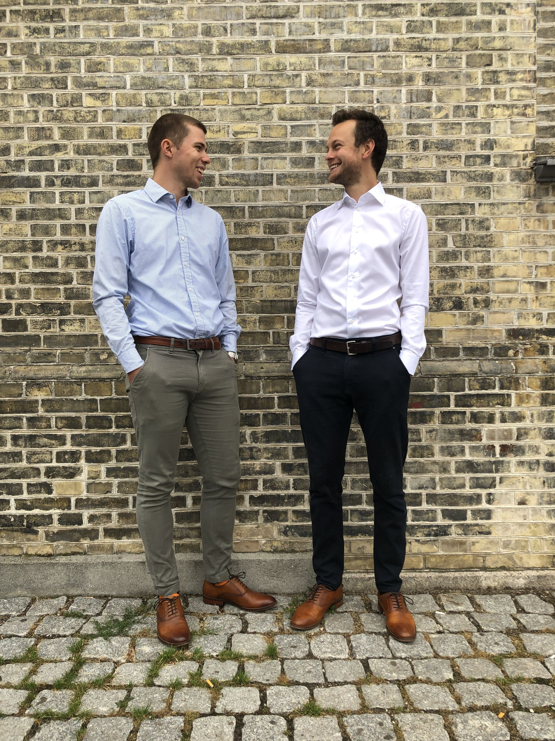 Two men in suits standing up against a wall